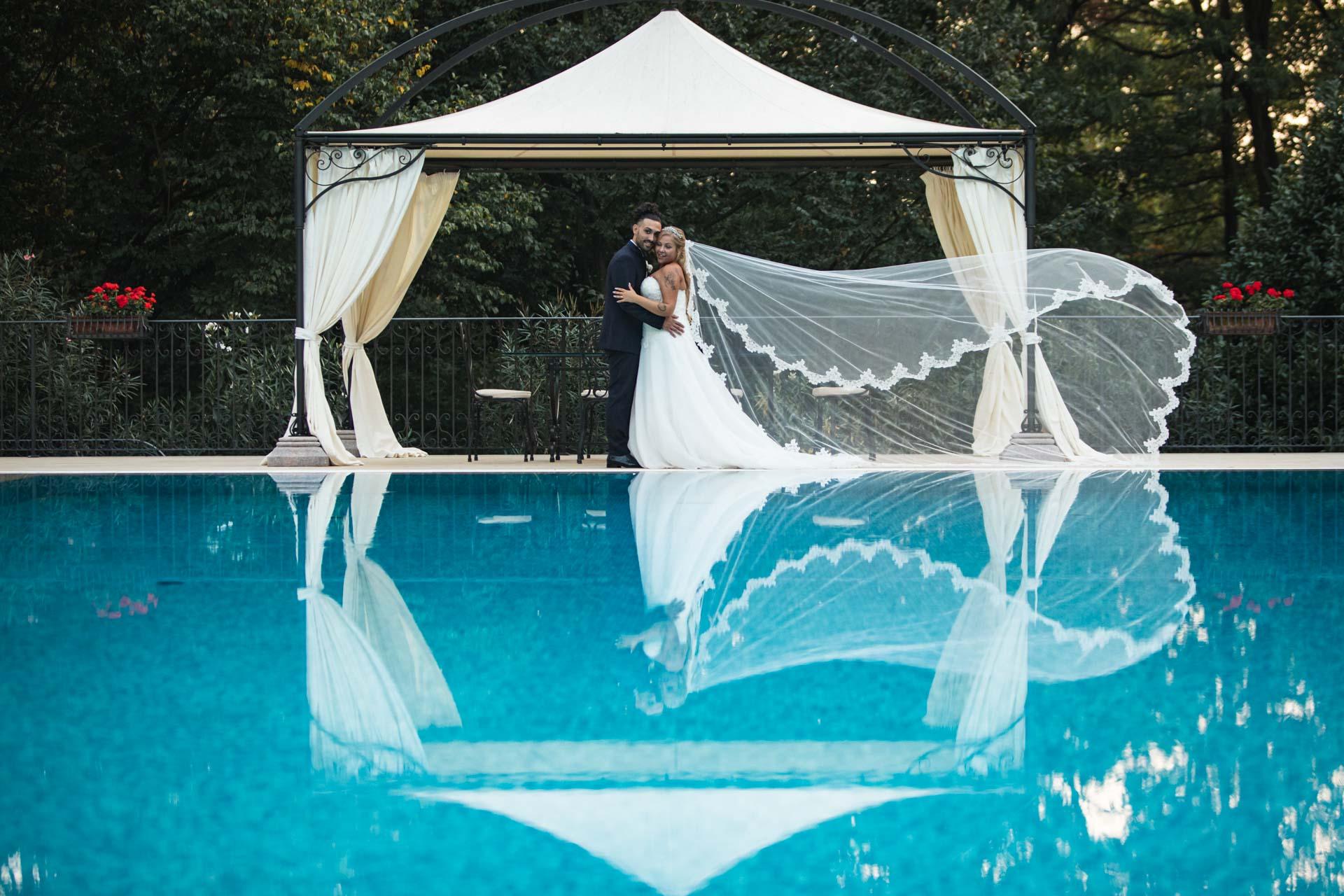 Sposi abbraccio velo piscina
