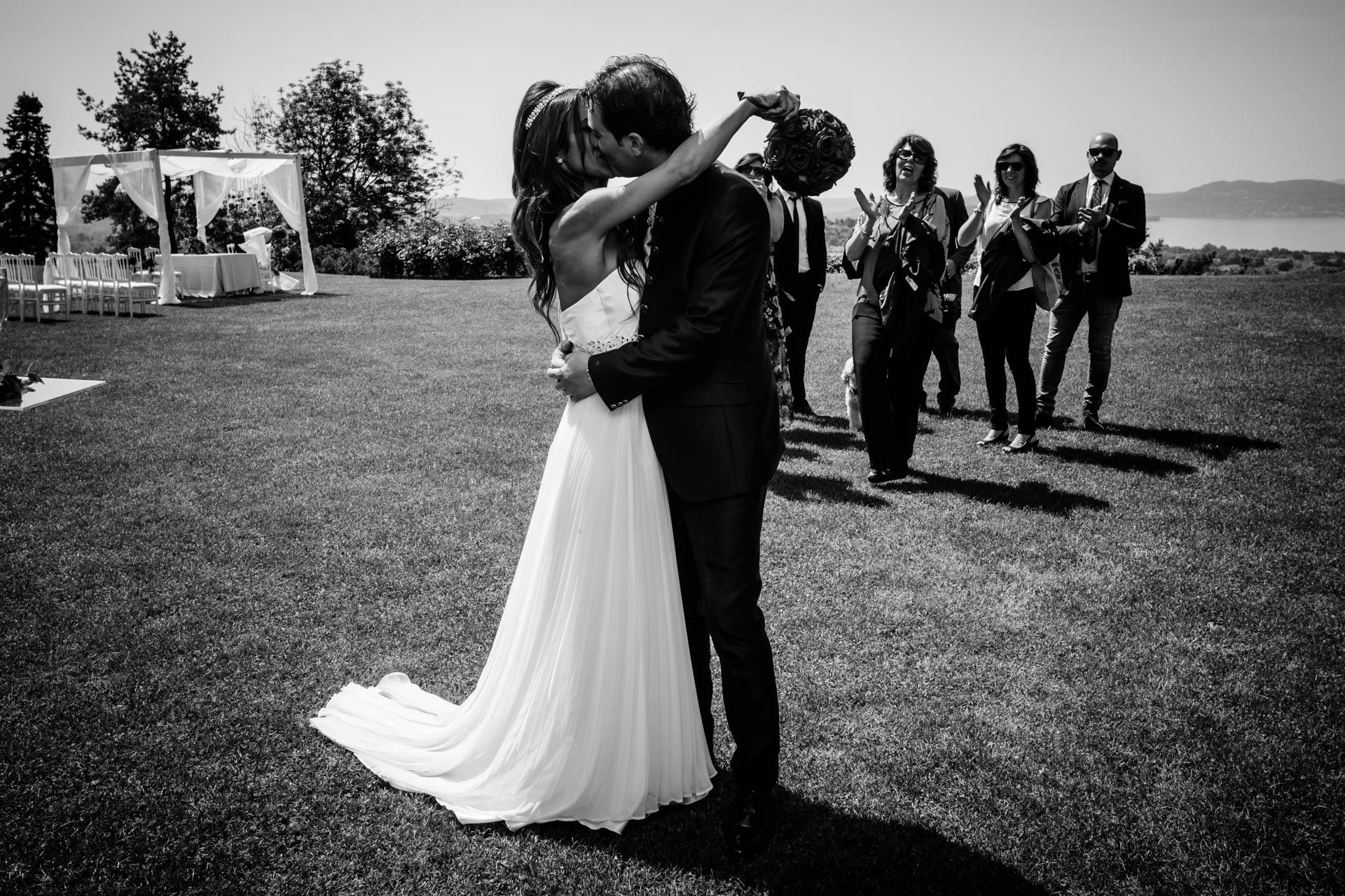 sposi bacio invitati ricevimento bianco nero